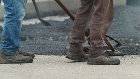 De arbeiders creëren nieuw asfalt - wegenbouw in stad stock video