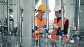 De arbeiders die brouwerijmachines controleren, sluiten omhoog stock videobeelden