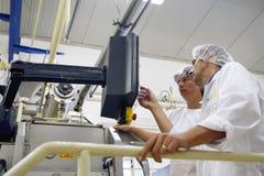 De arbeiders die van de fabriek het controlebord in werking stellen Stock Fotografie