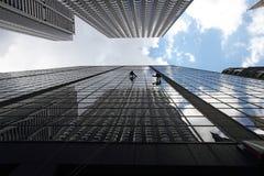 De arbeiders die van het onderhoud buiten een wolkenkrabber beklimmen Stock Fotografie