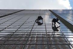 De arbeiders die van het onderhoud buiten een wolkenkrabber beklimmen Stock Afbeelding