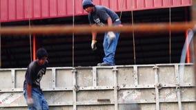 De arbeiders doen hand het werk het werpen emmer nat beton in het construeren van een schoolgebouw stock videobeelden