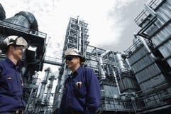 De arbeiders en de industrie van de raffinaderij royalty-vrije stock foto's