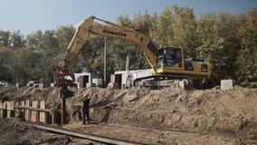 De arbeiders en het graafwerktuig op een bouwwerf stapelen het drijven in de grond op, pijpleidingsbouw stock footage