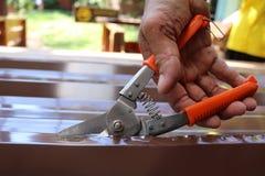 De arbeiders gebruiken schaar om het metaalblad voor dakwerk te snijden stock afbeelding