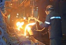 De arbeiders giet heet metaal in de vorm stock afbeelding