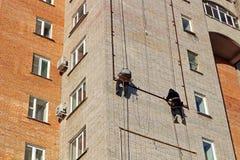 De arbeiders hangen de reclame op een gebouw stock afbeelding