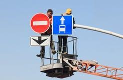 De arbeiders hangen verkeersteken stock foto