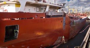 De arbeiders herstellen en schilderen schip bij drijvend dok bij de scheepswerf Schipschilders op het werk Boot die timelapse 4k  stock videobeelden