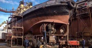 De arbeiders herstellen oud schip bij drijvend dok bij de scheepswerf De wederopbouw van de schippropeller Vissersbootlassen stock footage