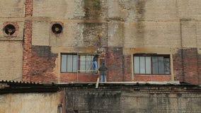 De arbeiders herstellen de voorgevel van een industrieel gebouw stock videobeelden