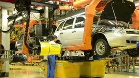 De arbeiders installeren de wielen op de auto Lada Kalina van fabriek AutoVAZ stock videobeelden