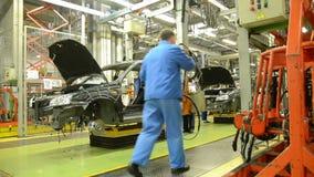De arbeiders installeren het absorptievat op de auto Lada Kalina van fabriek AutoVAZ stock videobeelden