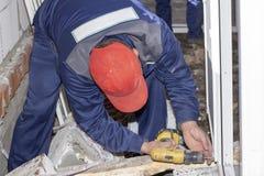 De arbeiders installeren plastic de bouw van het venstershuis reparatie royalty-vrije stock afbeeldingen