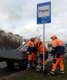 De arbeiders installeren verkeersteken op straat van Moskou Stock Foto's