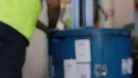 De arbeiders laden goederen op een vrachtwagen en genomen aan het pakhuis De arbeidersbestuurder van het werknemerspakhuis in een stock videobeelden