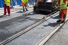 De arbeiders leggen asfaltweg en spoorlijnen aan Royalty-vrije Stock Afbeeldingen