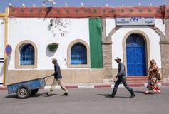 De arbeiders lopen langs een straat bij de haven van Essaouira, Marokko Royalty-vrije Stock Afbeelding