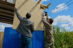 De arbeiders maken een dak in een buitenhuis stock afbeelding