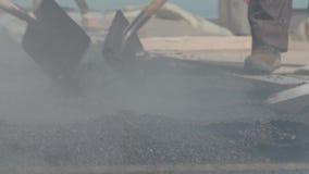 De arbeiders mengen heet asfalt terwijl het aanleggen van een weg stock videobeelden
