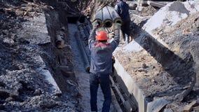 De arbeiders met bouwkraan zetten nieuwe waterpijpen met concrete plakken