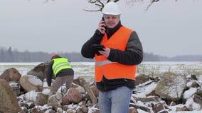 De arbeiders met cel telefoneren en voorhamer stock videobeelden