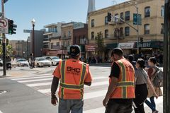 De arbeiders met oranje vesten wachten om een straat in San Francisco, Californië, de V.S. te kruisen royalty-vrije stock fotografie