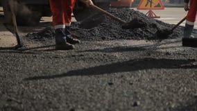 De arbeiders op de weg herstellen asfalt stock footage