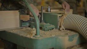 De arbeiders op de zaagmolen veranderen de snijders in de scherpende machine en de opstelling de machine voor houtverwerking, clo stock video