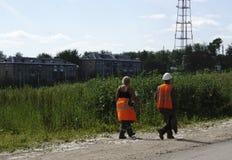 De arbeiders in oranje overall zijn terug van lunch stock foto's