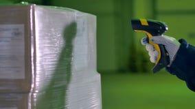 De arbeiders overhandigen met het aftastengoederen van de Streepjescodescanner bij een pakhuis 4K stock footage