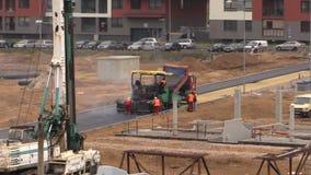 De arbeiders spreiden heet asfalt op weg in woonhuisdistrict uit stock videobeelden