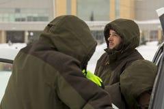 De arbeiders spreken bij de open deur van de auto stock foto