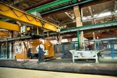 De arbeiders stellen machine bij het vullen van platen in werking Stock Afbeelding