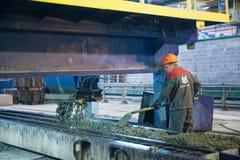 De arbeiders stelt machine bij het maken van platen in werking Stock Foto's