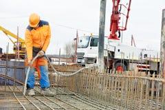 De arbeiders trillend beton van de bouwer in vorm Stock Fotografie