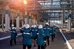 De arbeiders van chemische fabriek in werkkledij loopt dichtbij grote pijpleidingsbouw aan hun werkplaatsen royalty-vrije stock foto