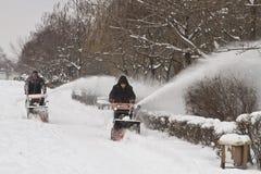 De arbeiders van de communale diensten verwijderen de sneeuw uit de stoep met behulp van gemotoriseerde voertuigen Stock Fotografie