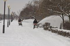 De arbeiders van de communale diensten verwijderen de sneeuw uit de stoep met behulp van gemotoriseerde voertuigen Stock Afbeelding