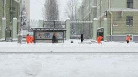 De arbeiders vegen sneeuw van stoep die in de winter, stoep van sneeuwonweer schoonmaken stock footage