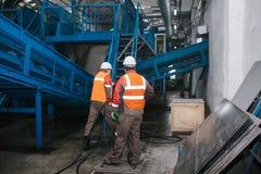 De arbeiders wassen materiaal bij de sorterende installatie royalty-vrije stock afbeeldingen
