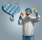 De arbeidersbouwer in helm beheert het bouwproces, kraanhaak Stock Afbeelding