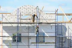 De arbeidersbouwers heffen bouwmaterialen op steiger op royalty-vrije stock foto's