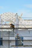 De arbeidersbouwers heffen bouwmaterialen op steiger op Stock Foto's