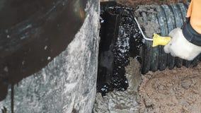 De arbeidershand zette teer op cementsteek tussen zwart plastic pijp en beton stock video