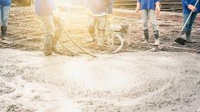 De arbeidersmens die een Trillingsmachine met behulp van voor elimineert bellen in beton na het Gieten van ready-mixed beton royalty-vrije stock foto