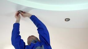 De arbeidersmens installeert of vervangt halogeen lichte lamp in plafond stock footage