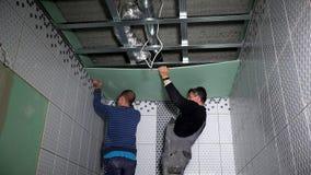 De arbeidersmensen hangen het blad van de gipsgipsplaat op plafond stock video