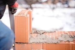 De arbeidersmetselaar die van de bouwmetselaar bakstenen muren met het mes van de troffelstopverf installeren Stock Foto