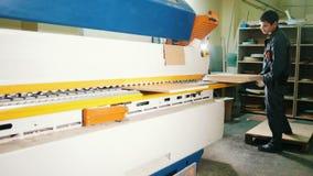 De arbeiderstimmerman behandelt houten raad op de scherpende machine op de meubilairfabriek stock footage